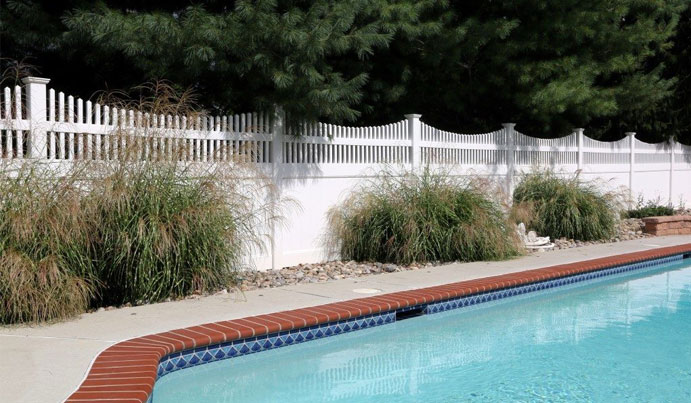 White vinyl pool fence design with landscaping