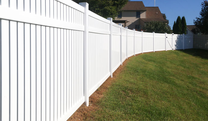 White vinyl privacy fence dividing two yards