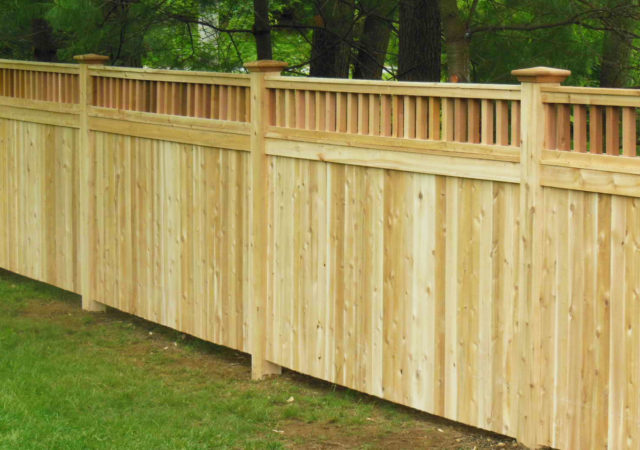 Solid privacy fence made of wood with detailed top