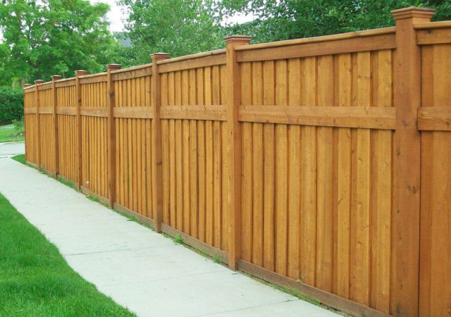Tall wooden privacy fence with cedar stain