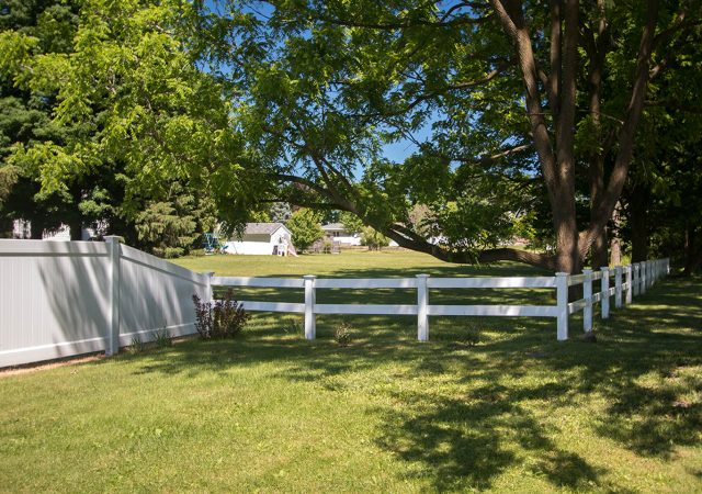 Two styles of vinyl fence meeting as one