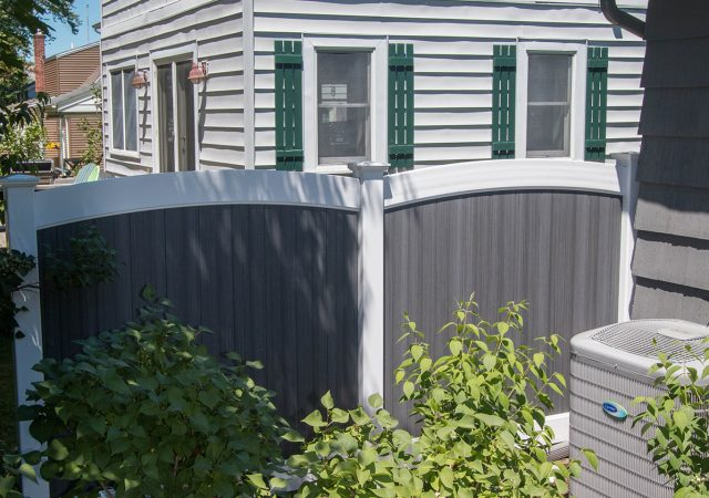 Curved top vinyl fence shared between neighbors