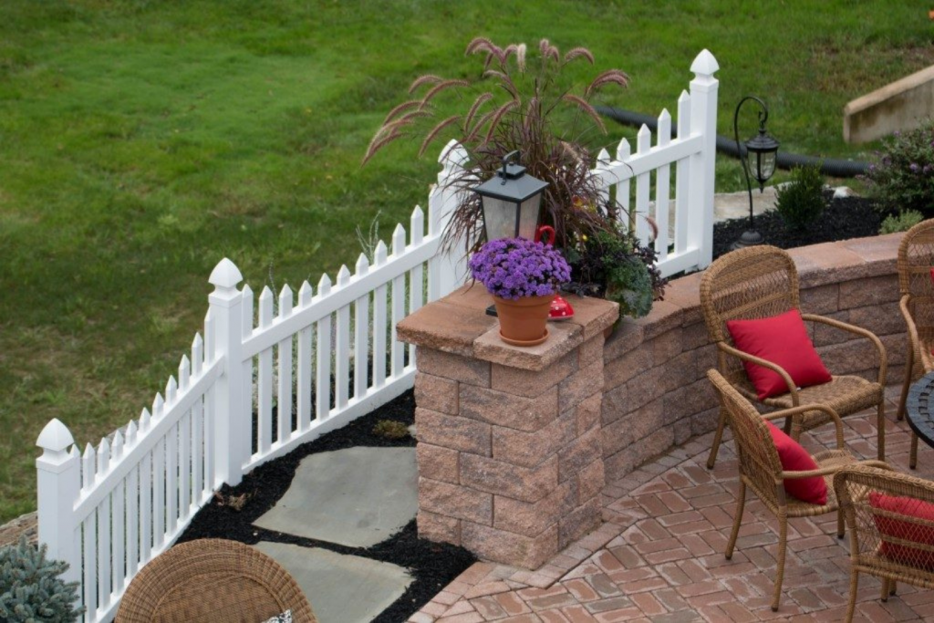 Landscaped patio with vinyl fence and stones