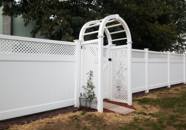 White vinyl fence with curved arbor at entry